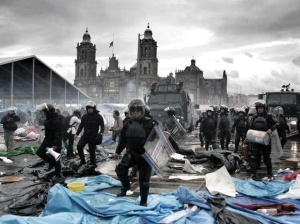 Riot police stomp on Mexico City's El Zocalo in front of a cathedral. Both the cathedral and the concrete sit on top of the sacred ruins of the Mexica Temples.