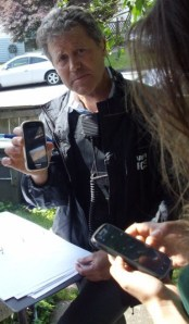 Image from Warrior Publications: VPD detective constable Rainey with one of the stolen cell phones taken during the June 3 raid.