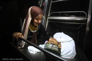 """Our honeymoon will never last my love!"" The fiancee of yesterday's martyr Abderrahman Al-Zamli having her last look at her martyred groom."