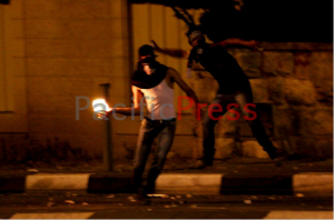 A masked Palestinian youth gets ready to throw a lit Molotov cocktail at the Israeli military checkpoint in front of him.