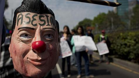 "A protester carries a hanging mask of Mexican President Enrique Pena Nieto marked with the word in Spanish ""Assassin"". Picture: AP/Rebecca Blackwell Source: AP"