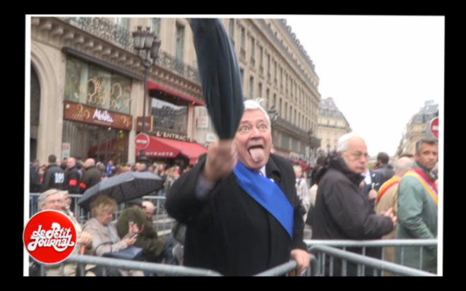 Front National European Deputy Bruno Gollnisch attacks journalists from French satirical news program Le Petit Journal with an umbrella. Gollnisch's attack incited FN party members to mob violence against the journalists (Screenshot from Le Petit Journal aired 4 May 2015).