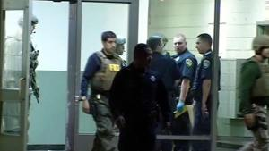 Assistant Police Chief Paul Figueroa wearing FBI identification during a raid of an Oakland residence in 2013