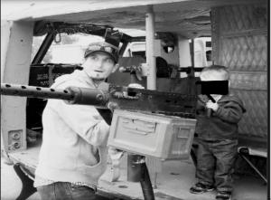 Officer Michael Lewelling teaching his 3 yr old son how shoot a 50 Cal machine gun